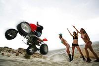 Three women watching a man on a ATV