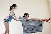 Woman pushing another woman in a shopping cart