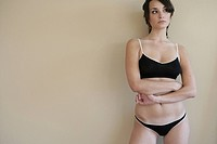 Woman in underwear standing against a wall