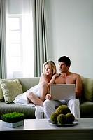 Young couple sitting on couch and using laptop