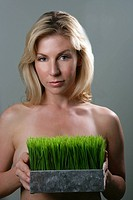 Topless woman holding pot of grass
