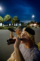 Friends drinking by a car at the parking area