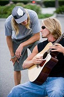 Man playing a guitar while conversing with his friend
