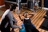 Trainer instructing a young woman with fitness ball in the gym
