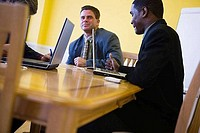 Businessmen in full suit conversing in an office