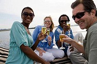 Portrait of cheerful friends toasting champagne on the deck of a boat