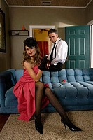 Mid adult man sitting by a young prostitute on sofa