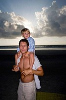 Young man with son on shoulders at the beach