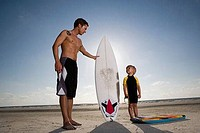 Father with his son standing by surfboard at the beach