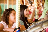 Teenage girls holding poles in a carousel