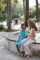 Mother and daughter sitting together by water fountain
