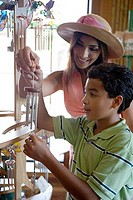 Young woman with her son holding a wind chime in store
