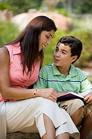 Young woman sitting with her son reading book