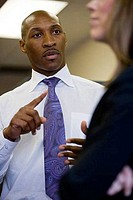 Businessman explaining to a businesswoman in an office