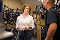 Woman talking to a man in a bicycle shop