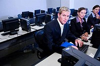 Portrait of business people using desktop pc in an office
