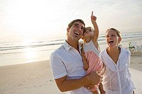 Cheerful young couple with daughter on the beach