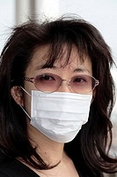 Woman wearing a face mask. Face masks are most often used in Japan by people who have colds, so as not to infect others, or to avoid catching infectio...