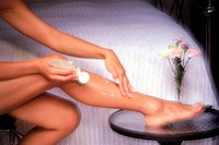 Woman applying moisturising cream to legs in bedroom