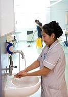 Hospital hygiene. Nurse washing her hands and cleaning mopping the floor in a hospital ward. Cleanliness in hospitals helps prevent the spread of hosp...