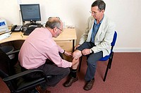 Knee examination. General practitioner examining a patient´s injured knee. Photographed in the UK.