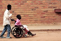 Patients outside a hospital. The boy pushing the wheelchair_bound boy has fractured his right arm. It has been set in a plaster cast, which is being s...