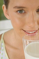 Close_up of young woman holding glass of milk