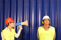 Mid adult woman shouting through a megaphone at a dock worker
