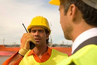 Male dock worker talking on a walkie-talkie (thumbnail)