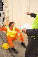 Mid section view of a businessman pointing to a male dock worker