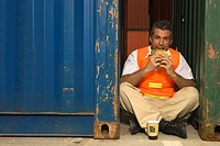 Portrait of a dock worker eating a sandwich