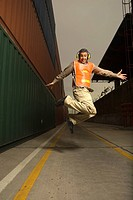 Dock worker wearing headphones and jumping at a commercial dock