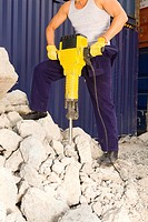 Low section view of a man operating a jackhammer