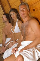 Young woman and a young man with a mature man having a sauna