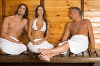 Young woman and a young man with a mature man having sauna