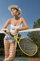 Young woman holding a tennis racket and standing in a tennis court
