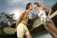 Young couple kissing each other in a tennis court