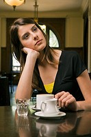 Close_up of a young woman sitting in a restaurant and thinking