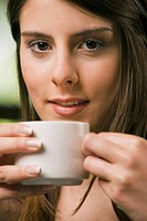Close_up of a young woman holding a cup of tea