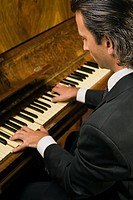 Close-up of a young man playing a piano (thumbnail)