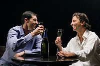 Two men holding champagne flutes and smiling