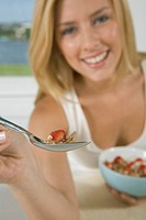 Close_up of woman holding spoonful of cereal