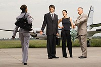 Two businessmen and businesswomen at an airport