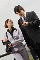 Businesswoman looking at a mobile phone in the hand of a businessman