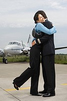 Young woman hugging a pilot at an airport