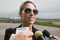 Close_up of a businesswoman giving interview at an airport