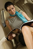 Businesswoman reading a magazine in a private airplane