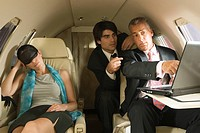 Two businessmen using a laptop with a businesswoman sleeping wearing a sleep mask