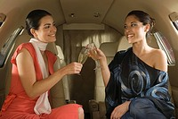 Two businesswomen sitting and toasting with champagne flutes in a private airplane