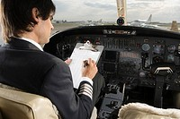 Rear view of a pilot holding a clipboard in the cockpit of a private airplane
